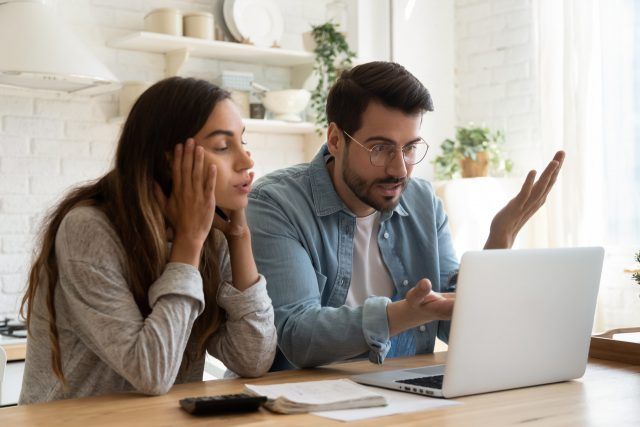 Zdenerwowana para przegląda historię płatności w bankowości online
